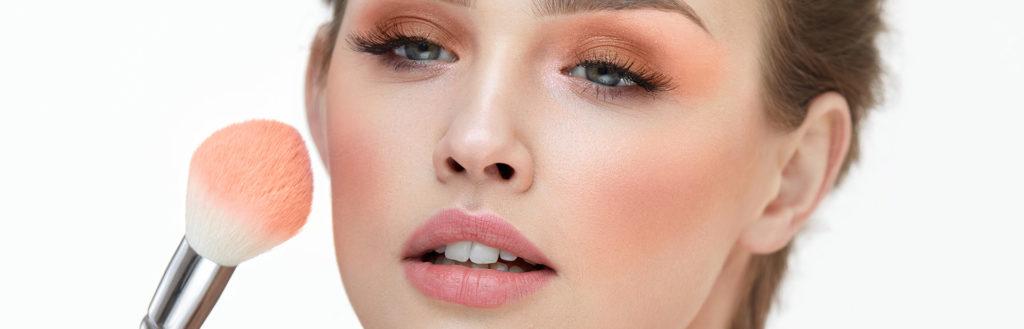 Na imagem o rosto de uma mulher com o blush aplicado. Ao lado direito partes do pincel de blush.