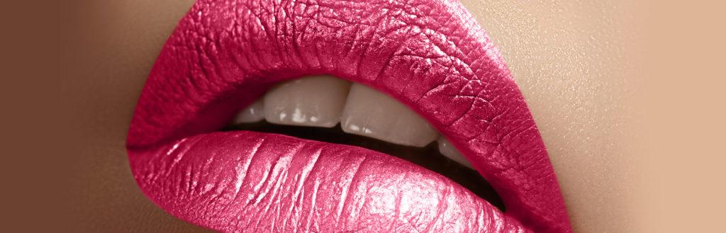 No centro da imagem uma boca, pintada com batom metalizado de tom rosa.