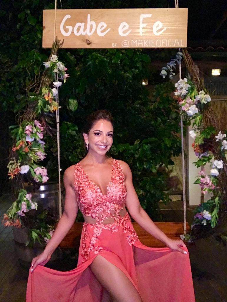 Imagem ilustrativa da madrinha à frente do balanço com o escrito Gabe e Fe by @makieoficial e ao fundo plantas decorativas, na matéria sobre maquiagem para madrinha de casamento.