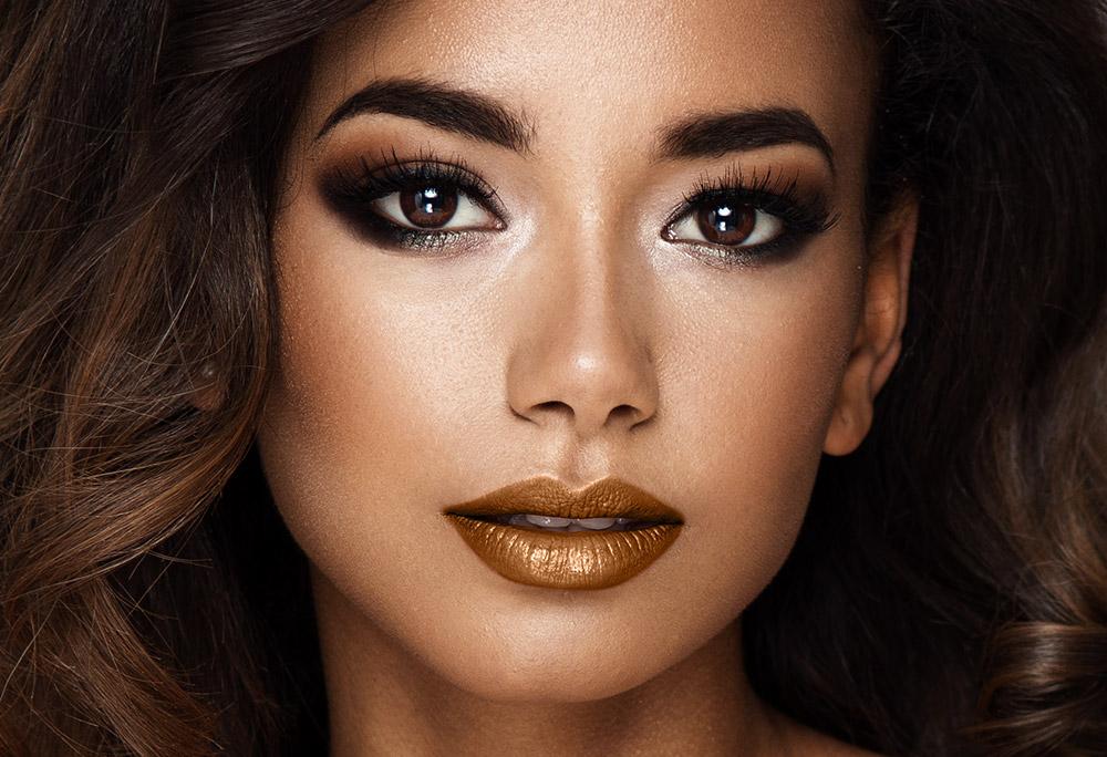 Na imagem o rosto de uma mulher com batom metlizado nos lábios, de tom dourado.