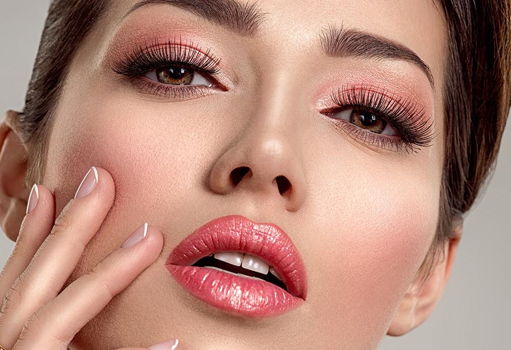 Na imagem o rosto de uma mulher com batom metlizado nos lábios, de tom coral.