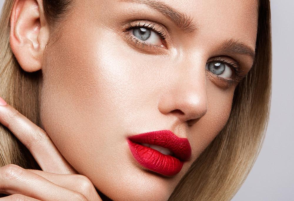Na imagem o rosto de uma mulher com batom metlizado nos lábios, de tom vermelho.