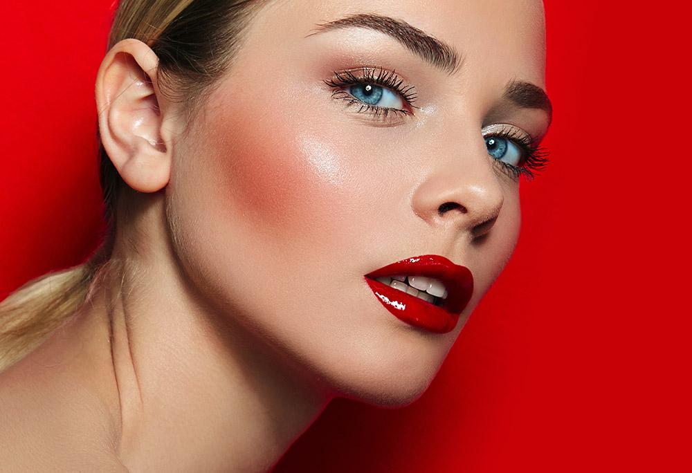 Imagem da maquiagem perfeita com destaque para o blush, sobre um fundo vermelho.