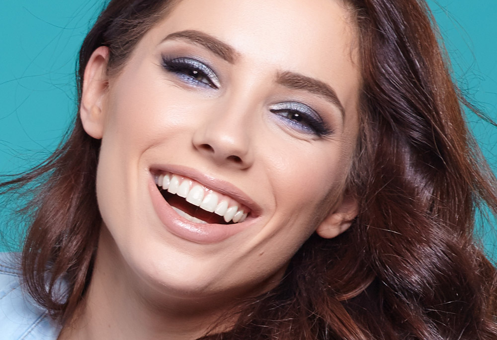 Imagem da maquiagem perfeita com pele natural, sobre um fundo azul.