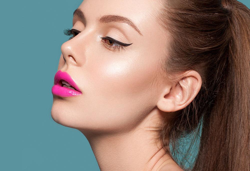 Imagem da maquiagem perfeita com delineador e gloss, sobre um fundo azul.