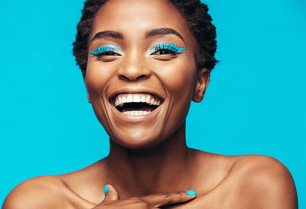 Imagem da maquiagem perfeita com efeito neon, sobre um fundo azul.