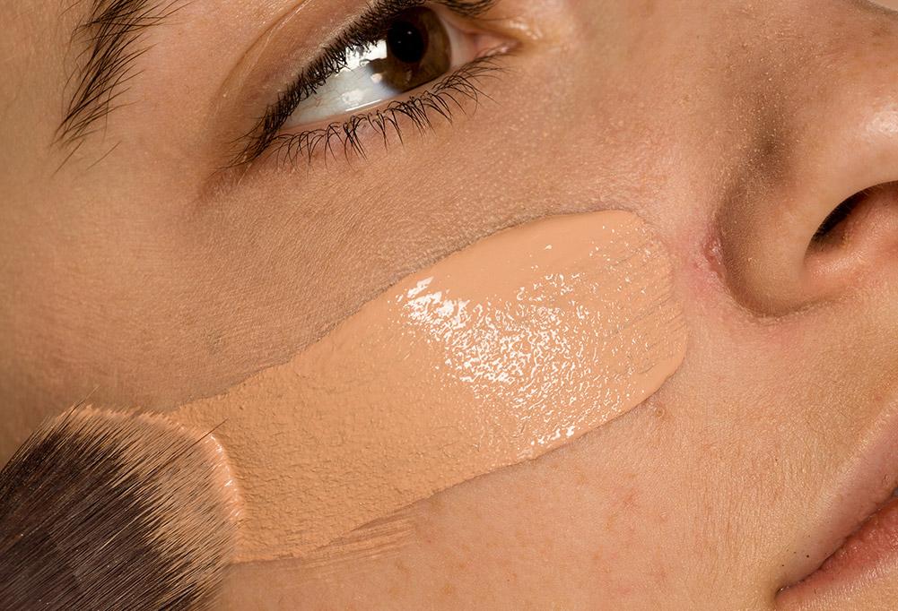 Base líquida aplicada no rosto de uma mulher.